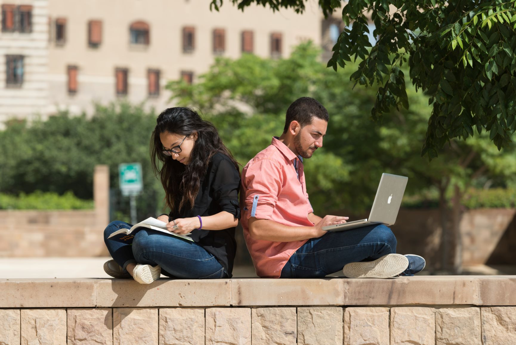two students studying on laptops